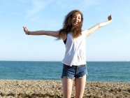 A cheerful teenage girl standing on the beach with her arms raised in exhilaration — Stock Photo