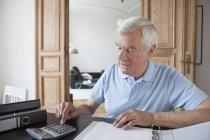 Último homem usando a calculadora para calcular as finanças domésticas na mesa — Fotografia de Stock