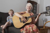 Retrato de niño sentado tocando la guitarra en el sofá en casa de la abuela - foto de stock