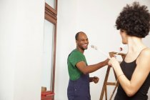 Playful couple having fun while painting apartment — Stock Photo