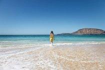 Задній вид жінка прогулянки по воді на тропічні пляжі — стокове фото