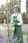 Smiling Mature woman holding watering can in garden — Stock Photo