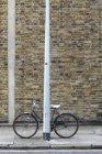 Bicyclette enfermée au poteau sur le trottoir — Photo de stock