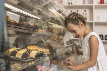 Side view of girl admiring dessert in bakery shop — Stock Photo