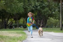 Fille courir avec chien à travers le parc — Photo de stock