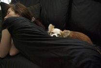 Женщина с собакой спит на черном диване — стоковое фото