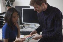 Jeunes collègues d'affaires masculins et féminins choisissant la couleur des échantillons dans le bureau — Photo de stock
