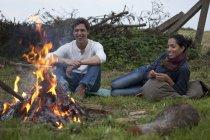 Молода пара, сидячи в табір вогню в природі — стокове фото