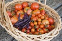 Inquadratura dal basso di pomodoro fresco e fagioli viola in cestino di vimini al tavolo rustico — Foto stock