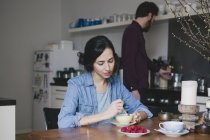 Young woman stirring coffee at kitchen table with man on background — Stock Photo