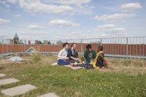 Amigos, pasar tiempo libre en la terraza jardín - foto de stock