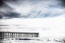 Vista in lontananza del molo sul mare contro il cielo nuvoloso — Foto stock