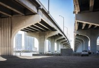 Underneath view of highway bridges and parked care — Stock Photo