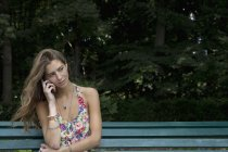 Young woman sitting on park bench and using mobile phone — Stock Photo