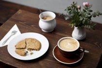 Un cookie e café latte servita sul tavolo con vaso di fiori — Foto stock