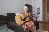 Senior mujer tocando la guitarra en la sala de estar en casa - foto de stock