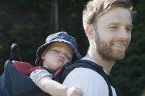 Усміхаючись батько здійснення спальний син у дитини перевізника — стокове фото