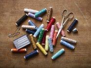 Vários carretéis da linha colorida na pilha com tesouras, alfinetes e agulhas de costura — Fotografia de Stock