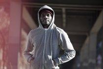 Young man in hooded sweatshirt standing under city bridge — Stock Photo