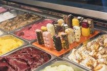 Крупный план различных мороженого в контейнерах на дисплее магазина — стоковое фото
