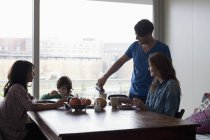 Happy family having breakfast at dining table in front of window — Stock Photo