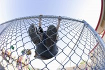 Вид с низкого угла на забор звена цепи лазания мальчика — стоковое фото