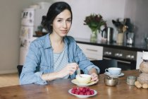 Ritratto di giovane donna felice che prende un caffè a tavola in cucina — Foto stock