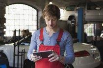 Mechaniker mit digital-Tablette in der garage — Stockfoto