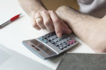 Close-up of male hands using calculator at table — Stock Photo