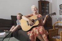 Niño juguetón sentado cantando mientras toca la guitarra en el sofá en casa de la abuela - foto de stock