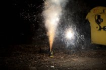 Sparks and smoke coming out of firework exploding on sidewalk — Stock Photo