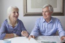 Счастливая пара старших с газетой, сидя за столом в доме — стоковое фото