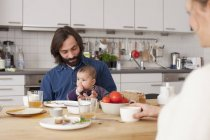 Family with baby girl having breakfast at home — Stock Photo