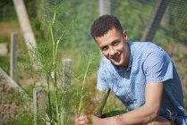 Portrait of handsome young man sitting at plant nursery — Stock Photo