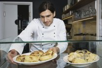 Мужчин шеф-повар принимая корицы рулоны для отображения розничной торговли в кафе — стоковое фото