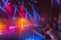 Man with sound mixer sitting by illuminated studio — Stock Photo