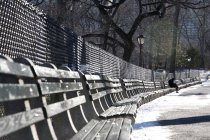 Distant view of person sitting on park bench in winter — Stock Photo