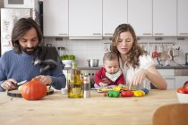 Father cutting vegetables with mother playing with baby girl in kitchen — Stock Photo