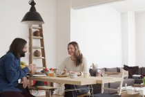 Smiling couple having breakfast at table in house — Stock Photo