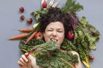 Портрет женщины, лежащей на овощах и кусающей листья ревеня на сером фоне — стоковое фото