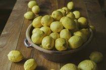 Крупным планом зрения лимонов в миске на сельских деревянный стол — стоковое фото