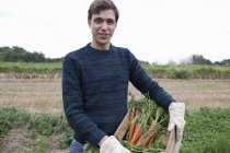 Portrait of smiling young Man holding harvested carrots in field — Stock Photo