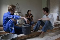 Men and woman sitting with paint bucket in apartment and talking — Stock Photo