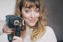 Ritratto di giovane donna sicura di sé con trapano elettrico a casa — Foto stock
