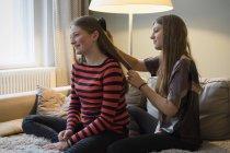 Молодая женщина расчесывает сестре волосы дома — стоковое фото