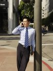 Businessman talking on mobile phone while leaning on post in city — Stock Photo