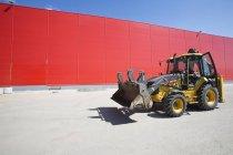 Bulldozer parcheggiato accanto alla facciata del magazzino rosso — Foto stock