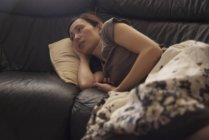 Mujer pensativa descansando en el sofá debajo de la manta — Stock Photo