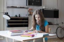 Chica enfocada estudiando en el escritorio en casa - foto de stock