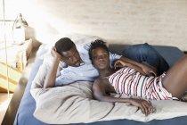 Портрет молодой афро-американской пары, отдыхающей в постели — стоковое фото